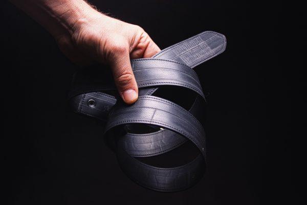 Gürtel aus Fahrradschlauch von ARTHURKOPF ohne spezielle Details in Hand vor schwarzem Hintergrund