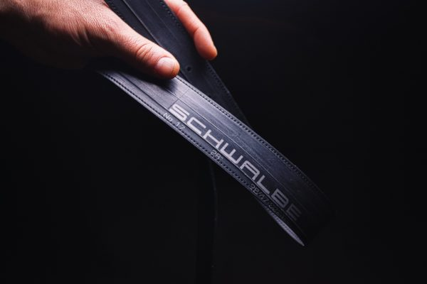 ARTHURKOPF Gürtel aus Fahrradschlauch mit Schwalbe Aufdruck in Hand vor schwarzem Hintergrund