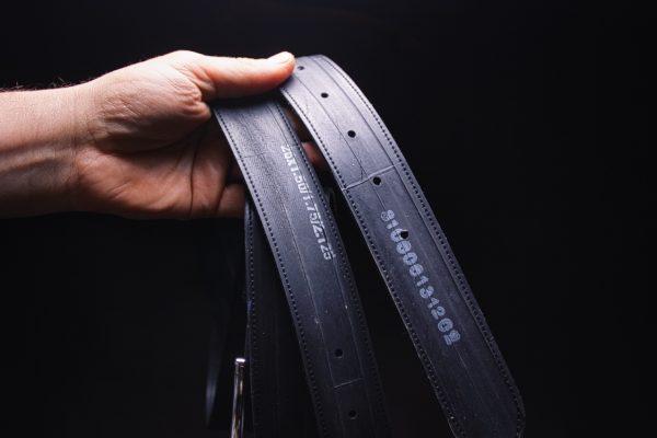 ARTHURKOPF Gürtel aus Fahrradschlauch mit Nummern Aufdruck in Hand vor schwarzem Hintergrund