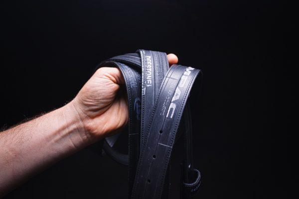 Mehrere Gürtel aus Fahrradschlauch von ARTHURKOPF mit verschiedenen Aufdrucken in Hand vor schwarzem Hintergrund