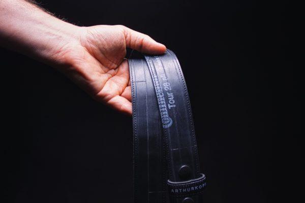ARTHURKOPF Gürtel aus Fahrradschlauch mit blauem Continental Aufdruck in Hand vor schwarzem Hintergrund