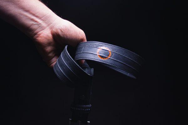 Gürtel aus Fahrradschlauch von ARTHURKOPF mit Flicken in Hand vor schwarzem Hintergrund